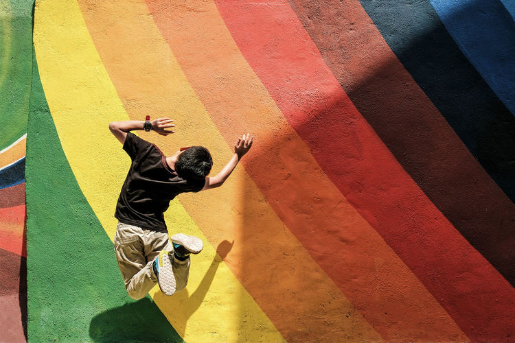 KayEL City Of Colours City Life Happiness Jump Paint Rainbow Colors Architecture Casual Clothing Colorful Full Length Jumping Leisure Activity Lifestyles Light And Shadow Motion One Boy Only Outdoors Shadow Skill  Wall - Building Feature Yellow Summer Sports #urbanana: The Urban Playground