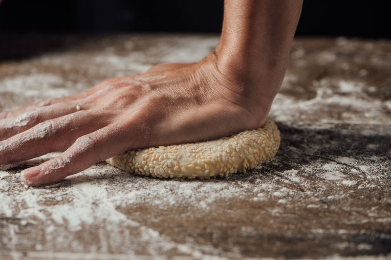 Cropped hand kneading dough on table