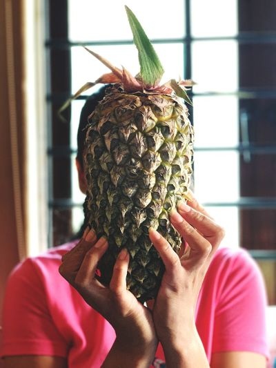 Woman holding pineapple against face while sitting at home
