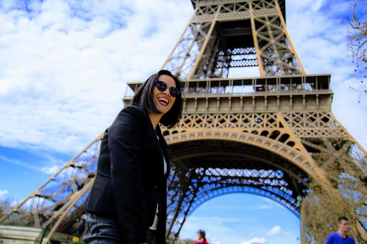 Low angle portrait of smiling woman standing against eiffel tower