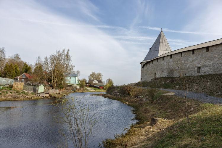 Buildings by river against sky