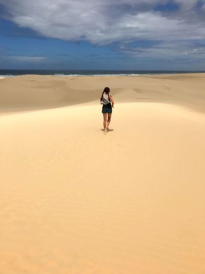 Rear view of woman running on sand dune at beach against cloudy sky