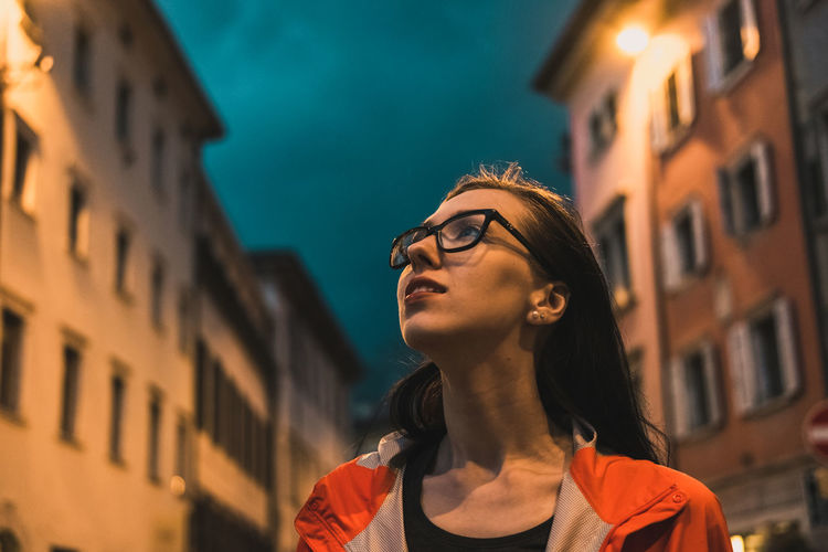 Young woman walking on street against sky at night