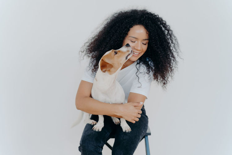 Smiling woman with dog sitting against white background