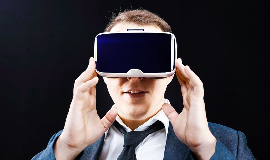 young man with VR glasses on Casual Clothing Cyberspace Front View Future Glasses Holding Interface Lifestyles Looking At Camera Real People Simulator Technology Virtual Reality Virtual Reality Simulator Vr