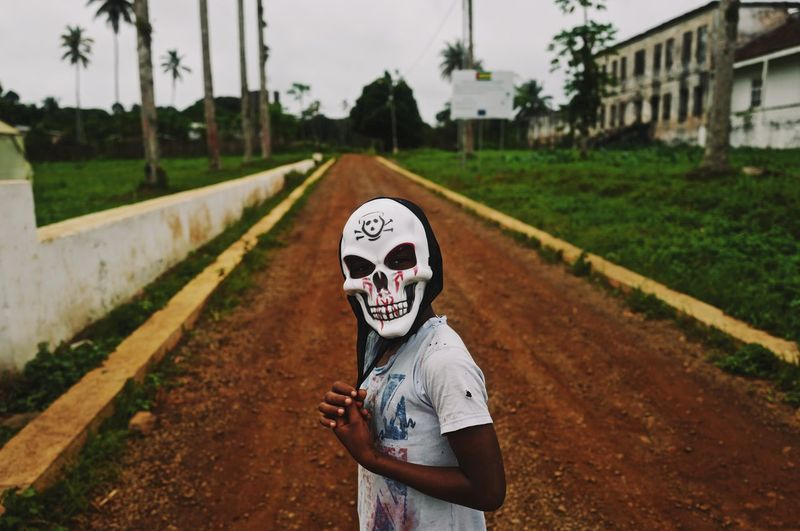 Person wearing mask standing by road