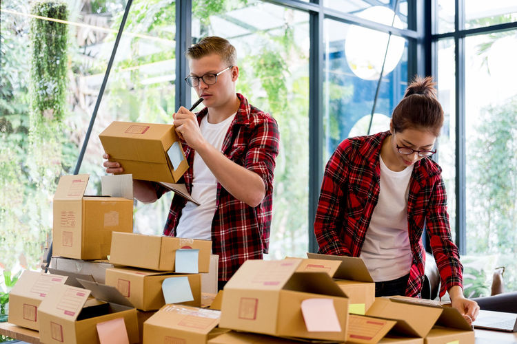 Coworkers packing boxes at desk in office