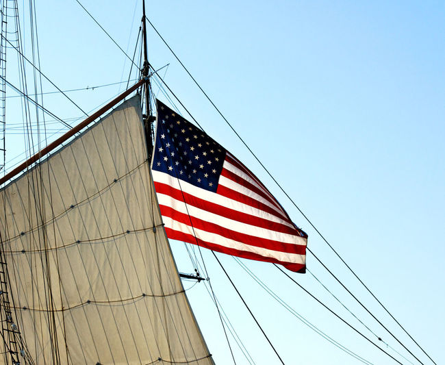 Low angle view of american flag on mast against clear blue sky