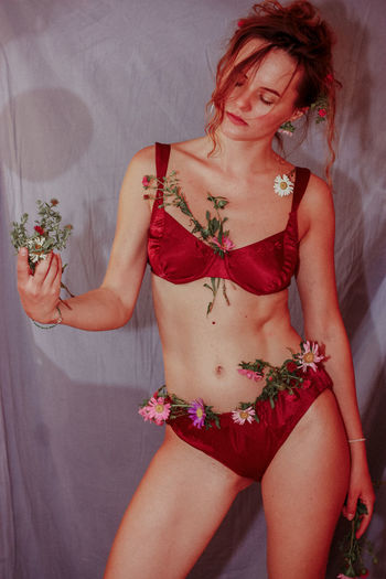 Midsection of woman with red flower