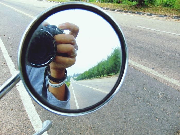 Close-up of man on side-view mirror