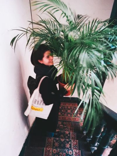 High angle view of woman standing by potted plant against wall