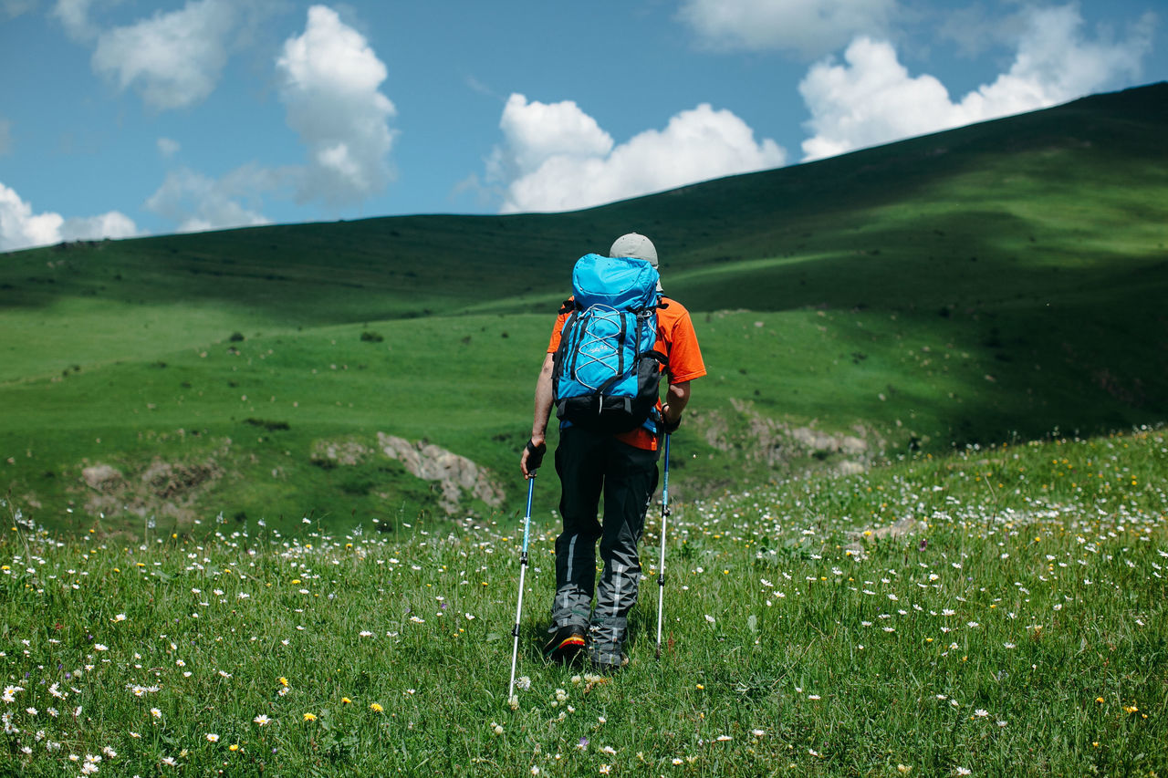 Low angle view of male hiker hiking on grassy mountain