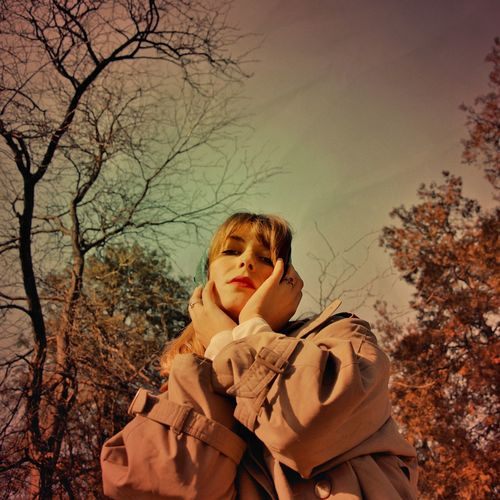 Portrait of happy girl on bare tree