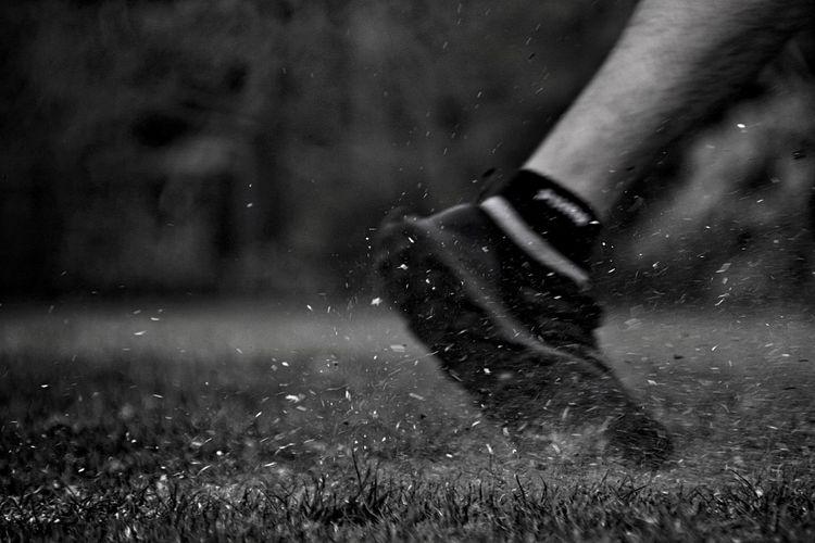Low section of man walking on field