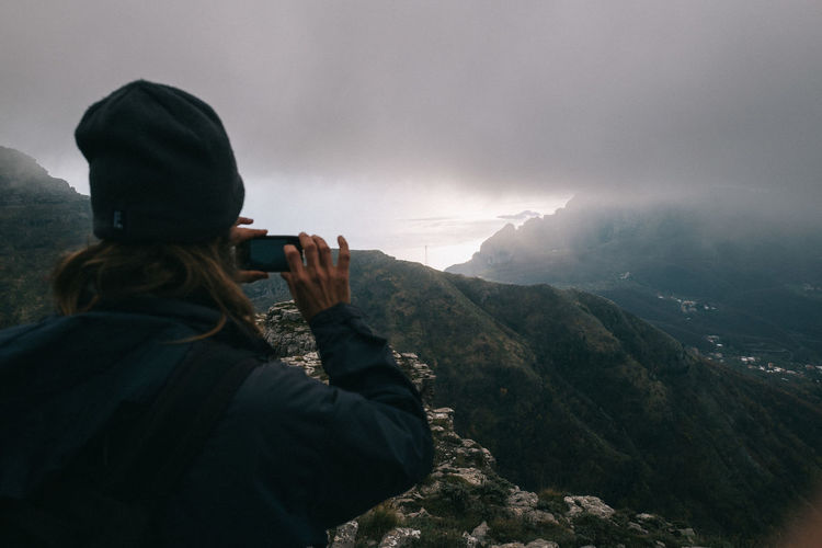 Rear view of woman photographing on mountain