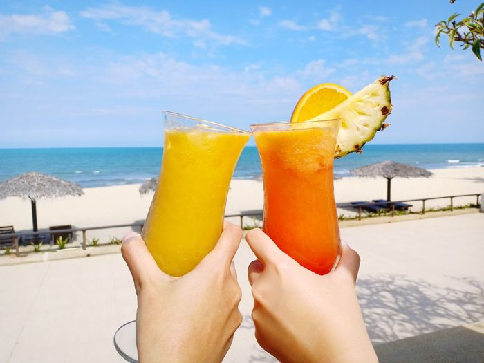 Cropped hands holding drinks against sea