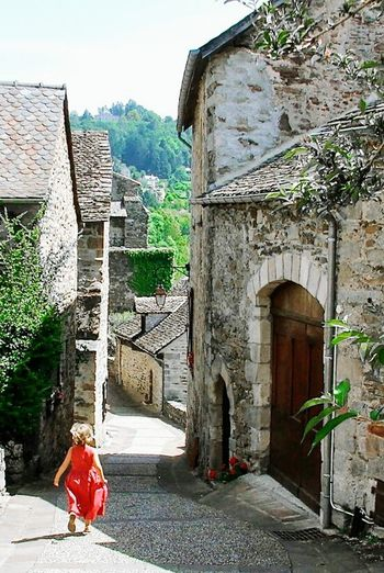 Girl in red dress running through the streets of Najac, France Outdoors Architecture French