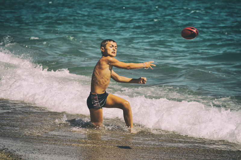 Boy Throwing Ball On Beach