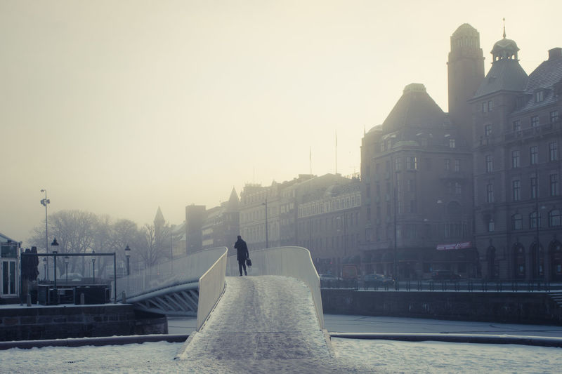 Rear view of person on footbridge against sky in city during winter