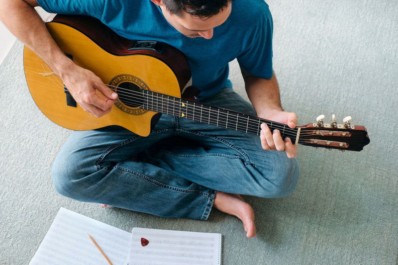 Midsection of man playing guitar against wall
