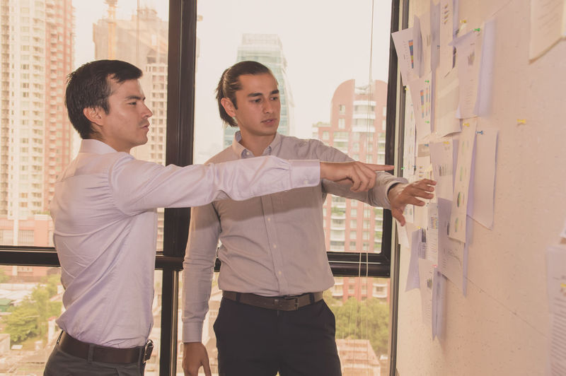 Businessman discussing graphs with colleague in office
