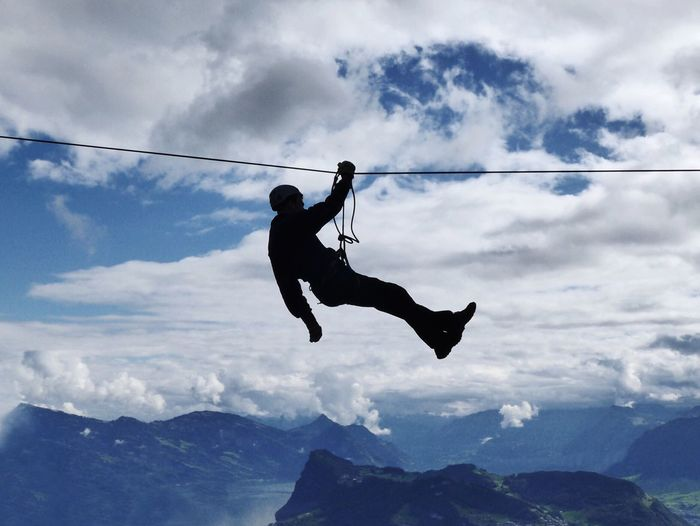 Silhouette Man Zip Lining Over Mountains Against Cloudy Sky