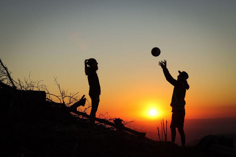 Silhouette people playing with ball against sky during sunset
