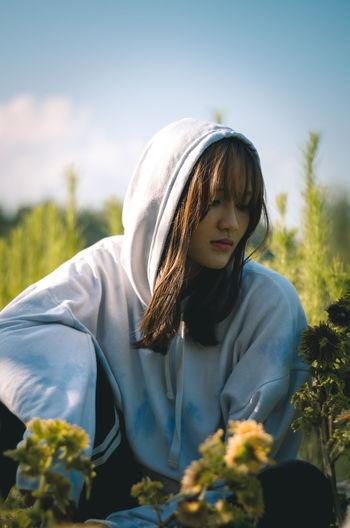 Beautiful woman standing by flowering plants against sky