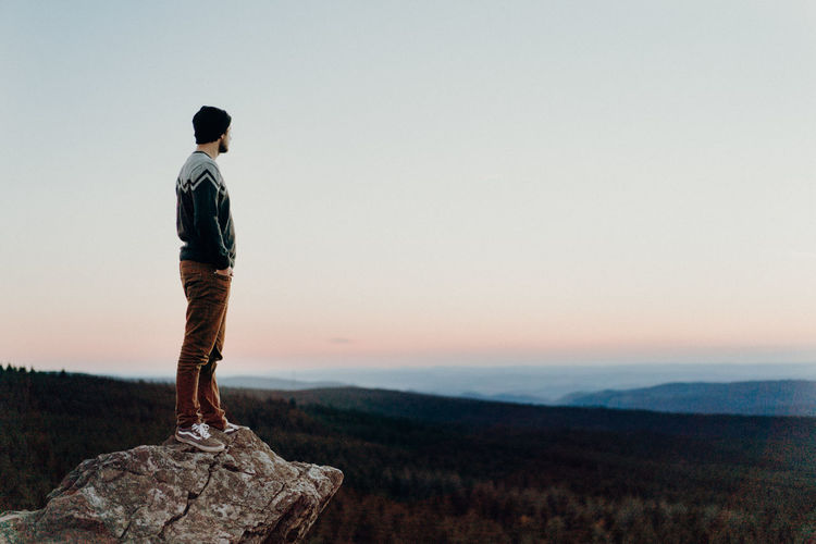 Man looking over forest after sunset One Person Standing Full Length Sky Leisure Activity Casual Clothing Lifestyles Sunset Scenics - Nature Beauty In Nature Men Rear View Nature Tranquility Mountain Real People Tranquil Scene Looking At View Rock Outdoors Summit