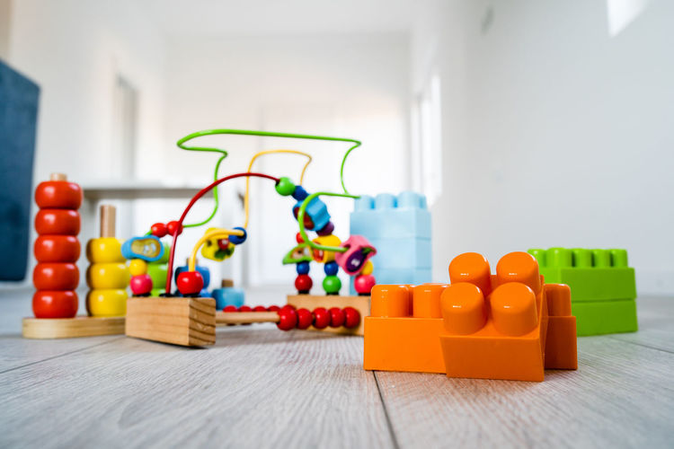Indoors  Toy Multi Colored Table No People Still Life Home Interior Wood - Material Large Group Of Objects Selective Focus Close-up Red Flooring Plastic In A Row Group Of Objects Focus On Foreground Toy Block Yellow