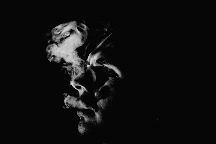 Close-up of man exhaling smoke against black background