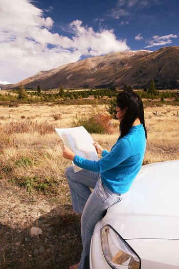 Woman reading map while sitting on car hood
