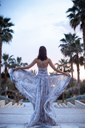 Rear view of woman standing against palm trees