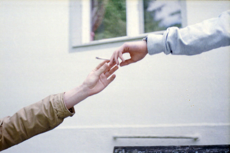Cropped Hand Giving Cigarette To Friend Against Window