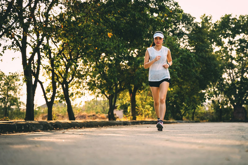 Woman runner does jogging on the city road. Sport and workout. Sport Workout Jogging Running Exercise One Person Tree Full Length Lifestyles Real People Plant Exercising Young Adult Leisure Activity Healthy Lifestyle Sports Clothing Day Nature Casual Clothing Clothing Road Outdoors Shorts Physical Activity
