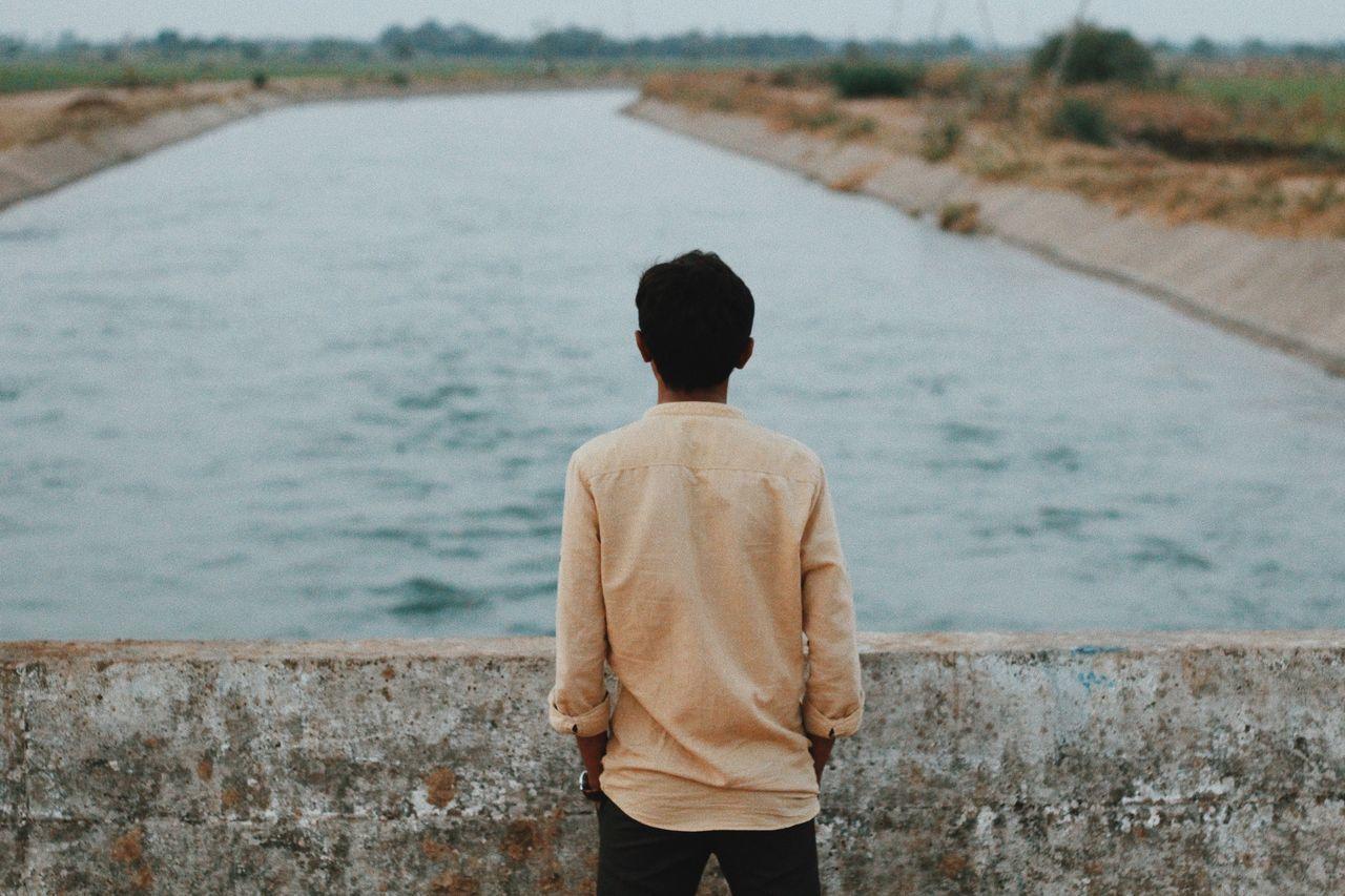 Rear View Of Man Looking At River