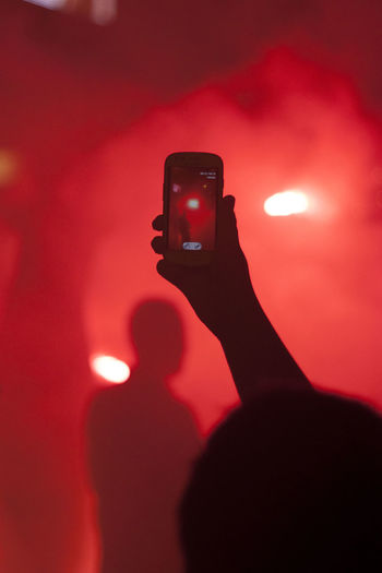 Shadow of man holding camera phone at music concert