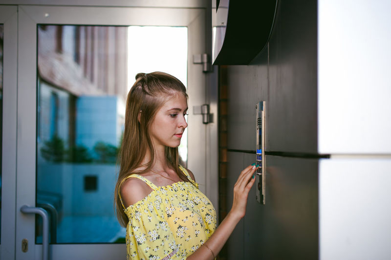 Young woman entering password on security system by door