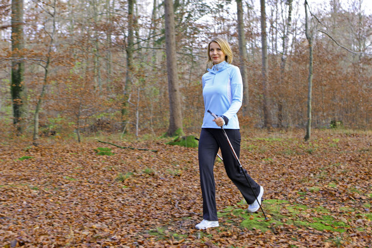Full Length Of Woman Walking With Hiking Poles In Forest
