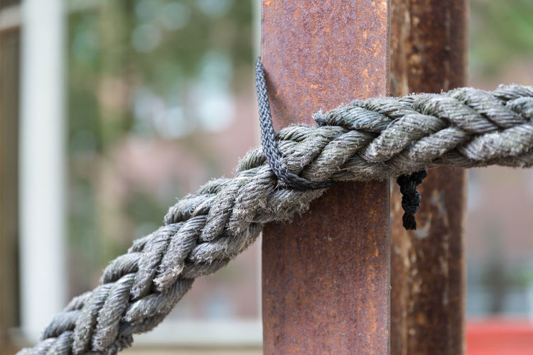 Close-up of rope tied on post