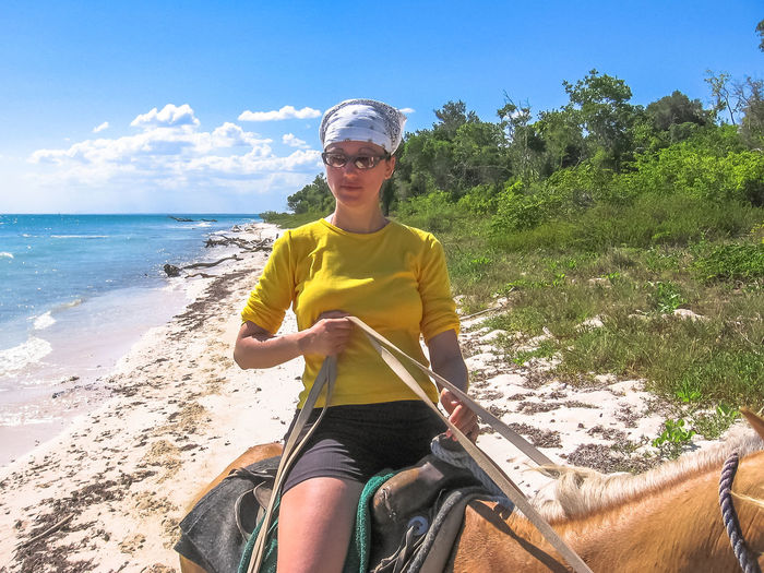 Side View Of Woman Riding Horse At Beach