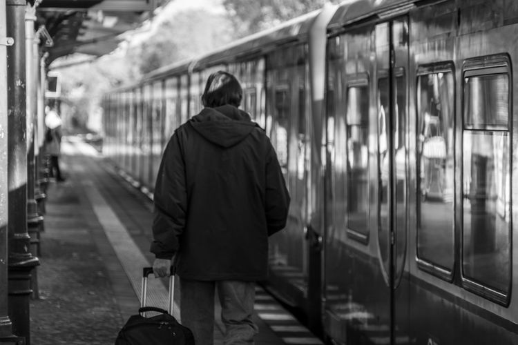 Rear view of man walking on train at railroad station