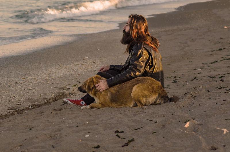 Man sitting on dog at beach