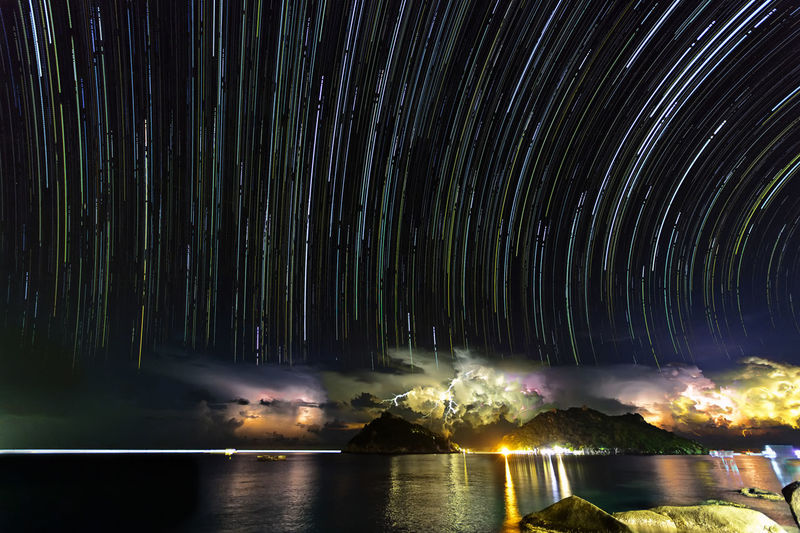 Star trails and thunder storm on Nang Yuan island, Thailand Astronomy Beauty In Nature Blurred Motion Flowing Water Illuminated Long Exposure Motion Nature Night No People Outdoors Power In Nature Scenics - Nature Sky Space Star - Space Star Trail Thunder Thunderstorm Tranquil Scene Tranquility Tree Water Waterfront