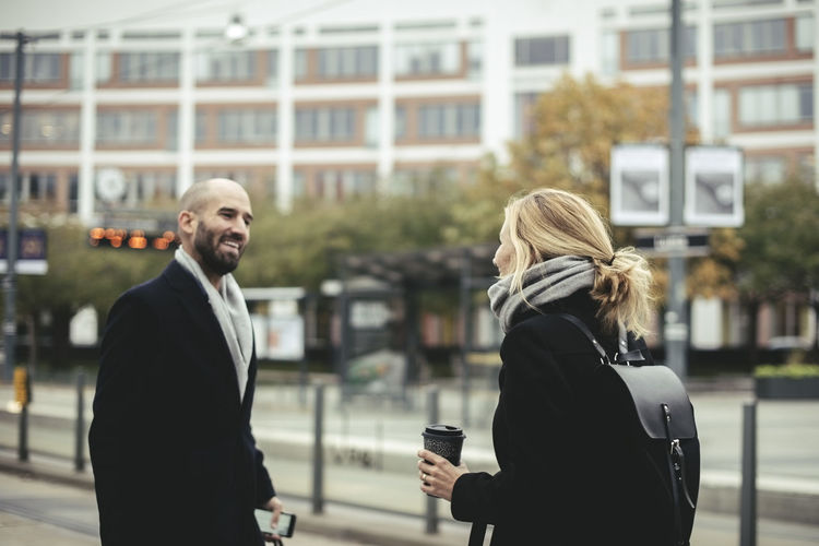 Man with woman standing on street in city