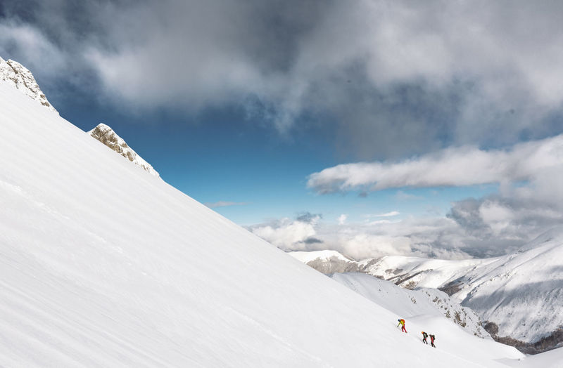 People climbing snowcapped mountains against sky