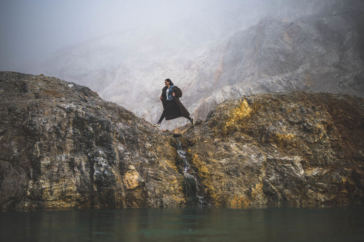 Woman on rock by lake against sky