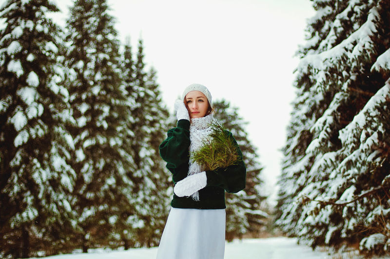 Redhead beautiful woman in green sweater and white gloves walking in the frozen winter forest.