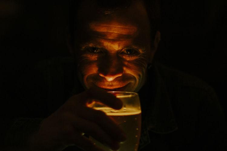Close-up portrait of smiling man holding alcoholic drink against black background