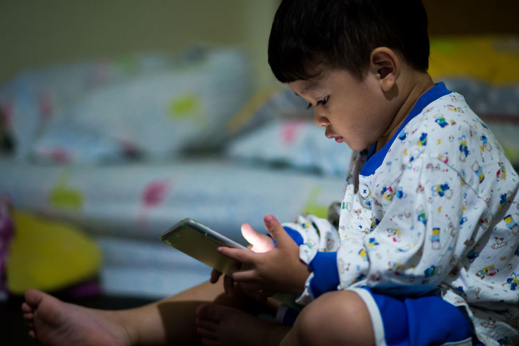 Cute Boy Using Mobile Phone At Home